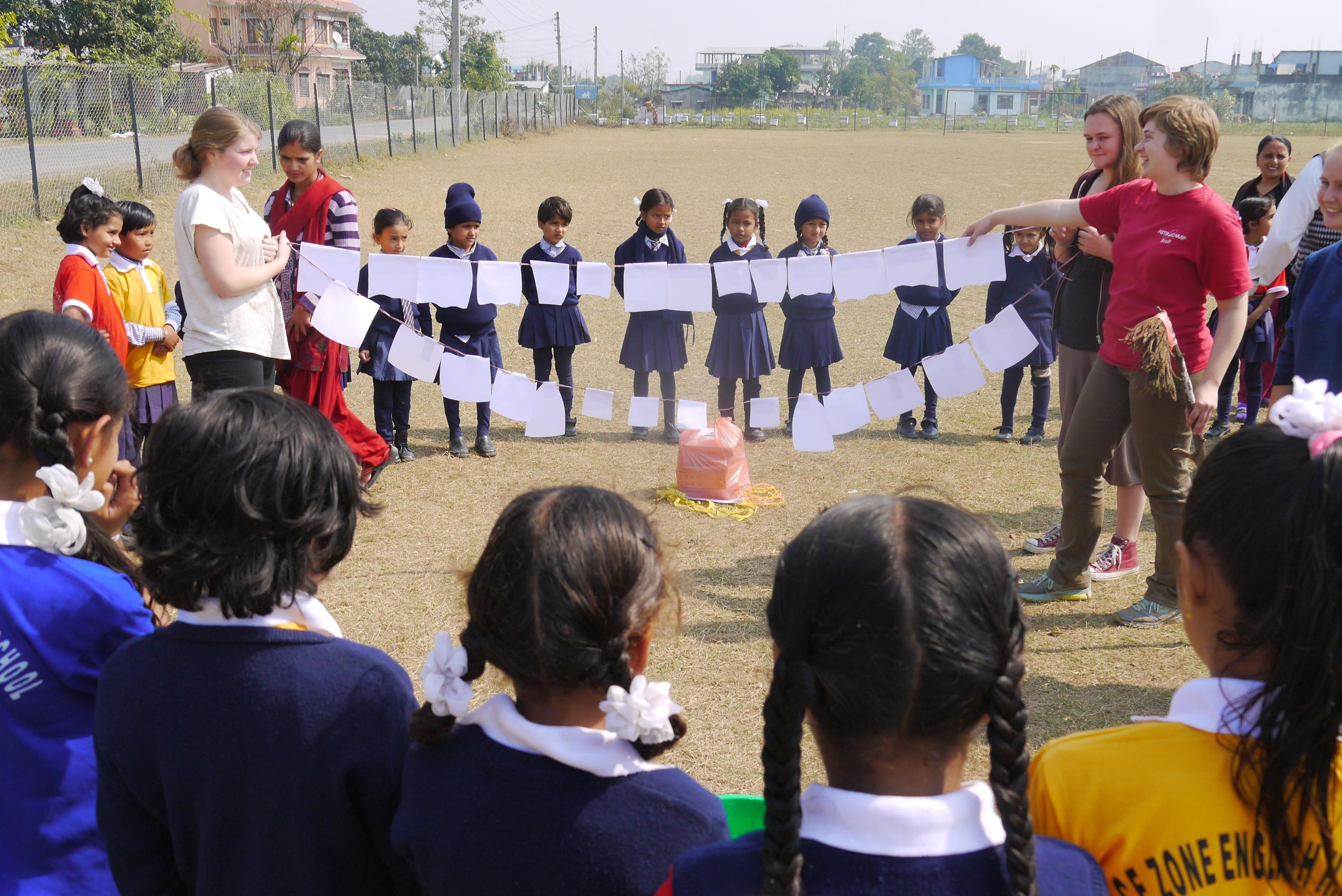 Projects Abroad volunteers working with children in Nepal are demonstrating how to brush your teeth in a school Childcare project.
